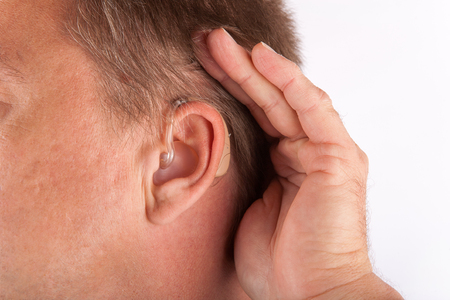 using senses: Ear of a man wearing hearing aid and cupping his hand behind his ear.