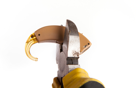 annihilate: Pincher tool destroying an old and used hearing aid