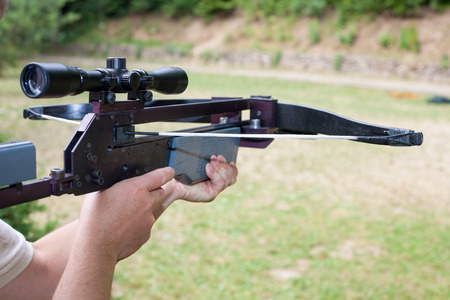 crossbow: Man holding a scoped crossbow