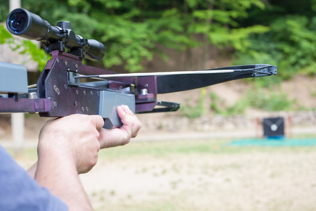 crossbow: Man targeting with a scoped crossbow