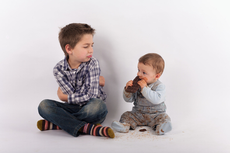 favoritism: Siblings conflict and favoritism concept - Baby eating a plate of chocolate white his brother looks at him with folded arms jealousy