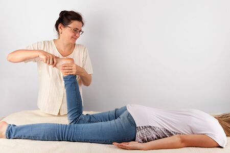 clothed: Bowen therapy of a young woman.  The bowen is a holistic system of healing Stock Photo