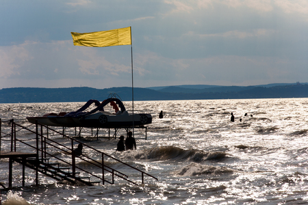 bather: Lake Balaton beach in backlight with silhouettes of bathers and paddle boats