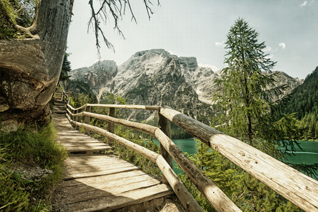 Hiking trail at Lake Braies in the Dolomites with the Seekofel mountain in the background, Sudtirol,Italy. (HDR image with black gold filter) Stock Photo