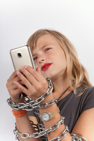 Smartphone addicted child - Girl with chain locked hands using a smartphone. Studio isolated on white background