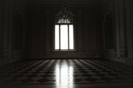 Window lit with mysterious white light in a spooky room built in baroque style. Stock Photo