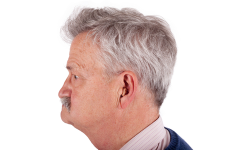 Portrait of a senior man wearing hearing aid. Studio isolated on white background. photo