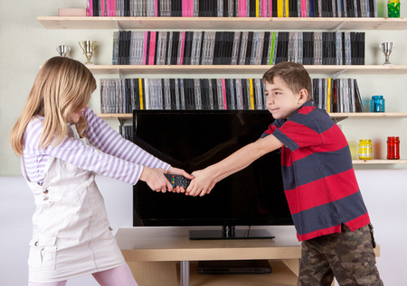 Siblings arguing over the remote control in the living room in front of the TV