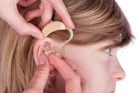 Close up of an ear and hands inserting a hearing aid into ear. Studio shot isolated on white.
