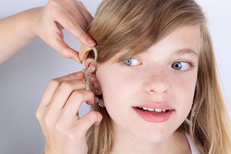 Portrait of a young girl trying hearing aids