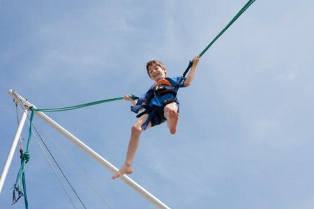 Young boy  enjoying jumping with trampoline jumping rope Stock Photo