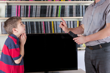 irresponsible: Strict dad with TV remote control not allowing watching the TV for his son Stock Photo