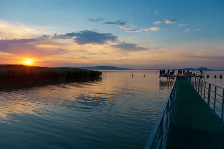bather: Sunset at Lake Balaton with pier and silhouettes in Hungary Stock Photo