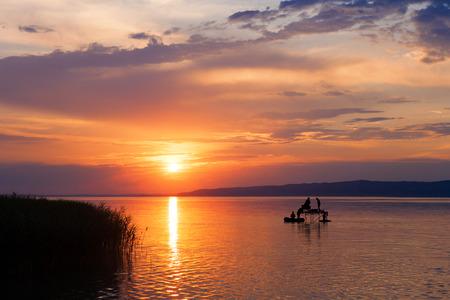 헝가리에서 낚시꾼 실루엣과 발라 톤 호수 위로 일몰 스톡 콘텐츠