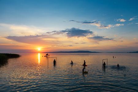 bather: Bathers silhouettes at sunset in Lake Balaton, Hungary Stock Photo
