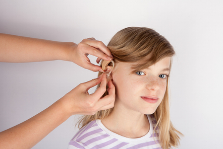 Adorable girl trying a hearing aid