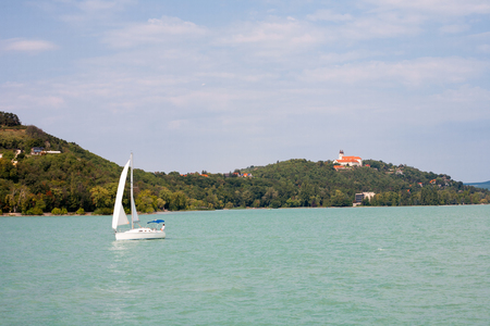 Tihany Peninsula with the Abbey and a sailboat viewed from a ships deck