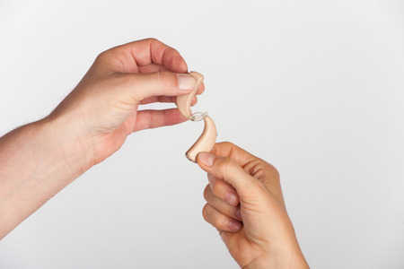 Hands connected by hearing aids
