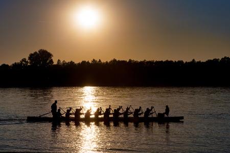 Schattenbild eines Drachebootes mit schaufelnden Leuten bei Sonnenuntergang auf der Donau