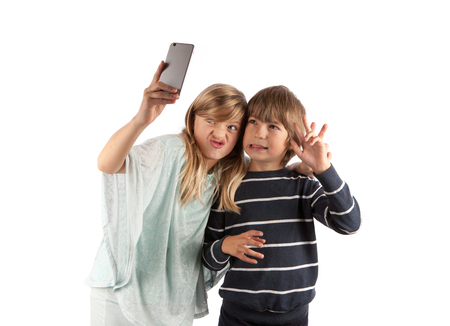 Funny kids taking a selfie with smartphone. Isolated on white. Stock Photo