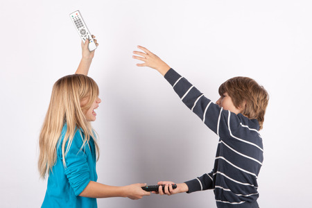Siblings fighting for TV remote controls