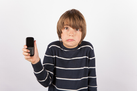 Young boy showing a simple phone is very upset because he would had like a smarthphone rather. 版權商用圖片