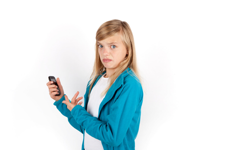 Young girl angry because she got only a simple mobile phone not a smartphone. Isolated on white.