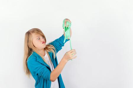 Schoolmeisje spelen met groene slijm ziet eruit als gunk