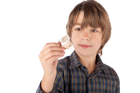 Cute young boy showing a hearing aid. Isolated on white background.