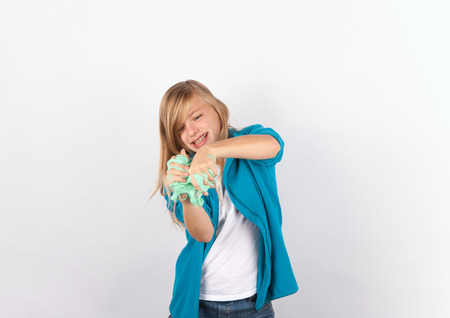Cheerful girl playing with slime