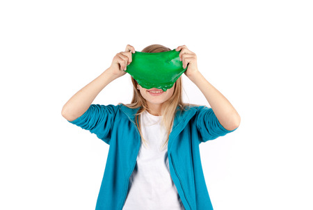 Funny girl holding a green slime looks like a disgusting thing in front of her face. Isolated on white background.