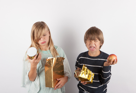 Children shocked by bad gifts. Stock Photo