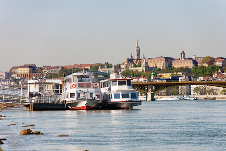 Buda Castle, FSt. Matthias church and Fishermen's Bastion viewed from Danube river with ships in the foreground Stock fotó