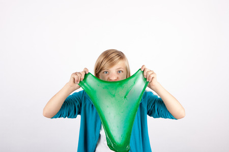 Funny girl holding green slime looks like gunk in front of her face.