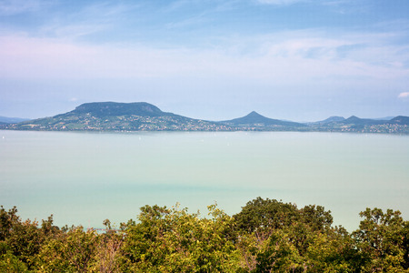 Lake Balaton viewed from the south coast with the Badacsony Mountain in the background and framed by trees in the foreground