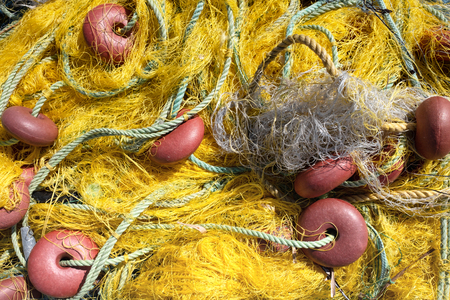 Yellow nylon fishing net with float line attached to small red plastic floats