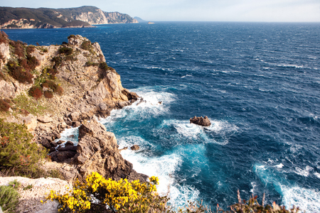 View of surging sea among cliffs with flowers in the front at Paleokastritsa in Corfu, Greece