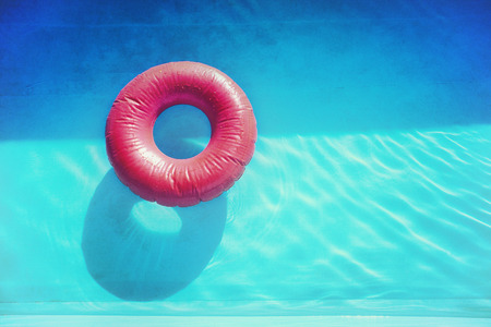 Retro style photo of a red inflatable swimming belt on a blue pool water