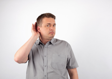 Deaf senior man cupping hand behind ear trying to hear Standard-Bild