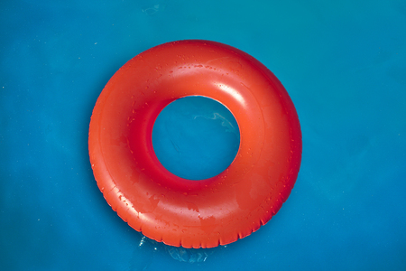 Red inflatable swimming tube on a blue pool water Stock Photo