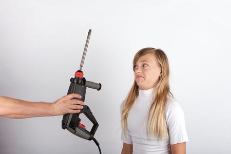 해머드릴을 든 손에 충격을 받은 어린 소녀 - 아이에게 적합한 도구이자 직업이 아닌 이 작품은 그녀에게 비현실적인 기대입니다. 스톡 콘텐츠