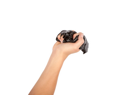 Hand squeezing black slime. Isolated on white background.