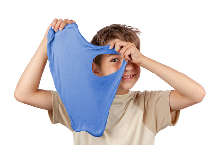 Cheerful boy holding a blue slime and looking through its hole. Studio isolated on white background. Standard-Bild