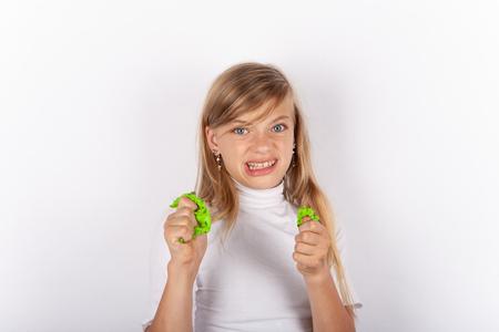 Nettes Mädchen, das Gesichter macht, während es grüne Schleime in ihren Händen drückt
