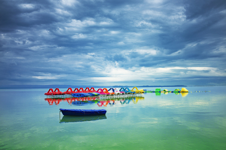 Lake Balaton before storm in Hungary. Tranquil scene with nice cloudscape, colorful pedalos and a blue boat in the front Stock fotó