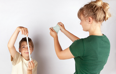 Siblings playing with slime toy strechting it