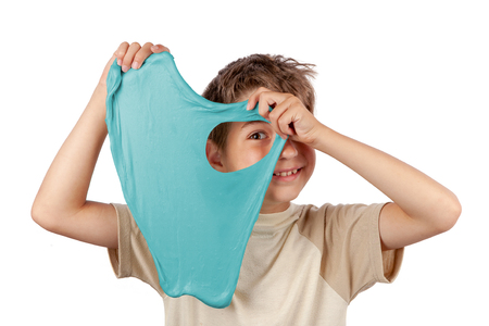 Cheerful boy holding a turquoise color slime toy and looking through its hole Фото со стока