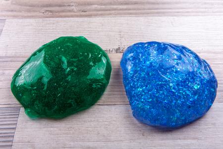 Green adn blue slime on a wooeden table