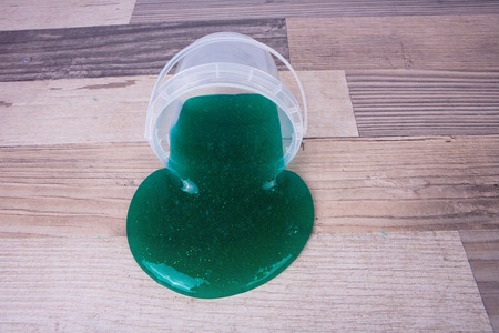 Green slime from a plastic bucket on a wooden table