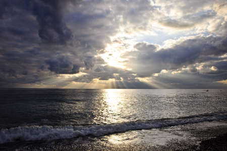 dramatic: Dramatic sunset over sea. Sunbeams passing through clouds. Stock Photo